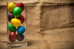 Ovos da páscoa coloridos em um vaso de vidro, fundo rústico fotos de stock