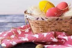 Ovos da páscoa coloridos em uma caixa da casca de vidoeiro, guardanapo em um fundo de madeira Estilo country Foto de Stock