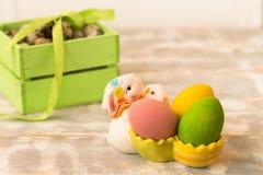 Ovos da páscoa coloridos em uma caixa de madeira, coelho, fitas em um fundo de madeira Estilo country Imagem de Stock Royalty Free