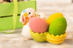 Ovos da páscoa coloridos em uma caixa de madeira, coelho, fitas em um fundo de madeira Estilo country Imagem de Stock