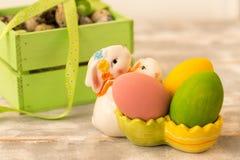 Ovos da páscoa coloridos em uma caixa de madeira, coelho, fitas em um fundo de madeira Estilo country Foto de Stock