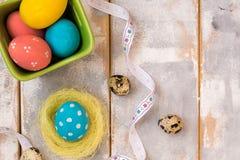 Ovos da páscoa coloridos em uma caixa de madeira e em um ninho, fitas em um fundo de madeira Estilo country Configuração lisa Cop Fotos de Stock