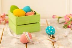 Ovos da páscoa coloridos em uma caixa de madeira, em fitas e em flores em um fundo de madeira Estilo country Imagens de Stock Royalty Free