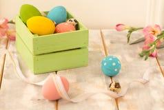 Ovos da páscoa coloridos em uma caixa de madeira, em fitas e em flores em um fundo de madeira Estilo country Imagem de Stock