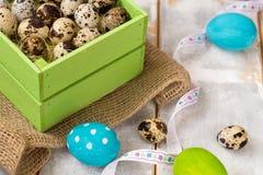 Ovos da páscoa coloridos em uma caixa de madeira, fitas em um fundo de madeira Estilo country Fotos de Stock