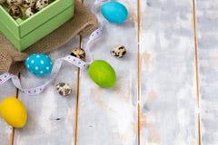 Ovos da páscoa coloridos em uma caixa de madeira, fitas em um fundo de madeira Estilo country Imagem de Stock