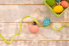 Ovos da páscoa coloridos em uma caixa de madeira, fitas em um fundo de madeira Estilo country Configuração lisa Imagem de Stock Royalty Free