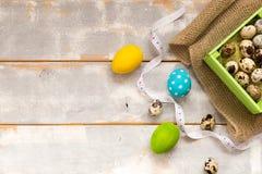 Ovos da páscoa coloridos em uma caixa de madeira, fitas em um fundo de madeira Estilo country Configuração lisa Espaço para o tex Imagens de Stock