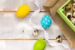 Ovos da páscoa coloridos em uma caixa de madeira, fitas em um fundo de madeira Estilo country Configuração lisa Espaço para o tex Fotografia de Stock Royalty Free