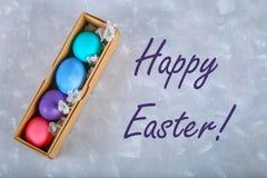 Ovos da páscoa coloridos em uma caixa de presente em um fundo concreto cinzento fotografia de stock royalty free