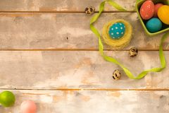 Ovos da páscoa coloridos em uma caixa e em um ninho verdes, fitas em um fundo de madeira Estilo rústico Configuração lisa Copie o Foto de Stock