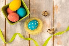 Ovos da páscoa coloridos em uma caixa e em um ninho verdes, fitas em um fundo de madeira Estilo rústico Configuração lisa Copie o Fotografia de Stock