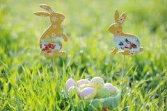 Ovos da páscoa coloridos em uma cesta com decorações do coelho Fotografia de Stock