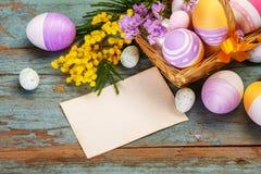 Ovos da páscoa coloridos em uma cesta e em flores da mola Fotografia de Stock