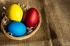 Ovos da páscoa coloridos em uma cesta em um fundo rústico imagem de stock royalty free