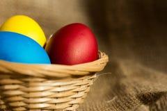 Ovos da páscoa coloridos em uma cesta em um fundo rústico fotos de stock royalty free