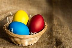Ovos da páscoa coloridos em uma cesta em um fundo rústico fotografia de stock