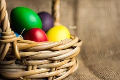 Ovos da páscoa coloridos em uma cesta, fundo rústico imagem de stock royalty free