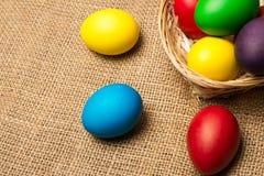 Ovos da páscoa coloridos em uma cesta, fundo rústico imagens de stock