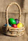 Ovos da páscoa coloridos em uma cesta, fundo rústico fotografia de stock