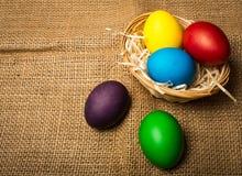Ovos da páscoa coloridos em uma cesta, fundo rústico fotos de stock royalty free