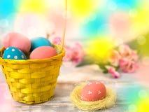 Ovos da páscoa coloridos em uma cesta tecida da palha, fita em um fundo de madeira Estilo country Copie o spase Foto de Stock Royalty Free