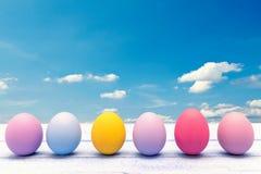 Ovos da páscoa coloridos em uma placa de madeira branca Imagens de Stock Royalty Free