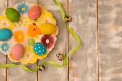 Ovos da páscoa coloridos em uma placa decorativa e fita em um fundo de madeira Estilo rústico Configuração lisa Espaço para o tex Fotos de Stock Royalty Free