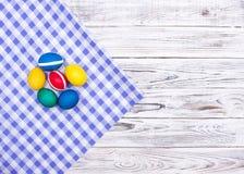 Ovos da páscoa coloridos da galinha na tela heterogêneo quadriculado e no fundo de madeira branco, espaço da cópia, decoraç foto de stock royalty free