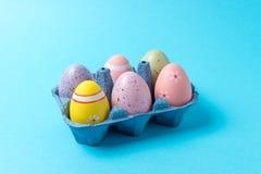 Ovos da páscoa coloridos na bandeja da caixa no fundo azul Conceito mínimo foto de stock royalty free