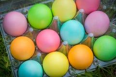 Ovos da páscoa coloridos na bandeja plástica velha na grama verde fotografia de stock royalty free