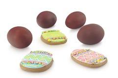 Ovos da páscoa coloridos na cebola marrom e nos especiaria-bolos multicoloured da Páscoa isolados no fundo branco Imagens de Stock