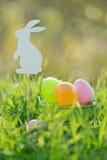 Ovos da páscoa coloridos na cesta acolchoada para fora com decorações do coelho Imagem de Stock Royalty Free