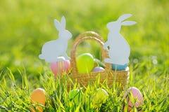 Ovos da páscoa coloridos na cesta acolchoada para fora com decorações do coelho Imagem de Stock
