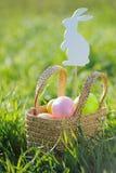 Ovos da páscoa coloridos na cesta acolchoada para fora com decorações do coelho Foto de Stock