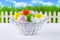 Ovos da páscoa coloridos na cesta, na cerca de madeira e na grama Fotografia de Stock