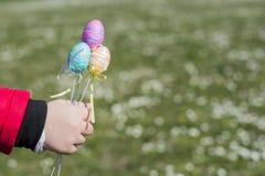 Ovos da páscoa coloridos nas mãos das crianças Fotografia de Stock Royalty Free