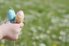 Ovos da páscoa coloridos nas mãos das crianças Fotos de Stock Royalty Free