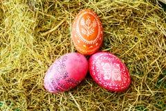 Ovos da páscoa coloridos no feno Fotos de Stock