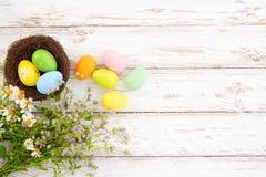Ovos da páscoa coloridos no ninho com a flor no fundo de madeira rústico das pranchas na pintura branca imagens de stock royalty free