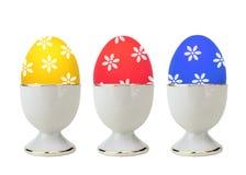 Ovos da páscoa coloridos no suporte isolado no branco imagem de stock