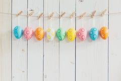 Ovos da páscoa coloridos que penduram no fundo branco de madeira rústico w Fotos de Stock