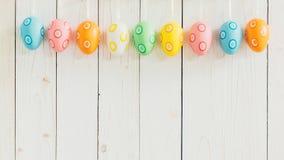 Ovos da páscoa coloridos que penduram no fundo branco de madeira rústico w Fotografia de Stock