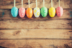 Ovos da páscoa coloridos que penduram no fundo de madeira rústico com sp Imagem de Stock Royalty Free