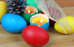 Ovos da páscoa coloridos, vela, chama Fotos de Stock
