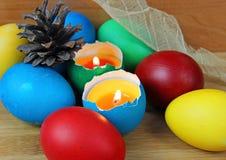 Ovos da páscoa coloridos, vela, chama Imagem de Stock