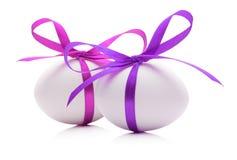 Ovos da páscoa com as fitas cor-de-rosa e roxas isoladas no branco Imagens de Stock