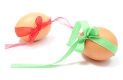 Ovos da páscoa com as fitas verdes e vermelhas. Fundo branco Imagem de Stock
