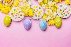 Ovos da páscoa com bolo e as flores bonitas dos narcisos amarelos no fundo cor-de-rosa, vista superior Fotografia de Stock