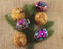 Ovos da páscoa com queques e ramo de árvore Fotografia de Stock Royalty Free